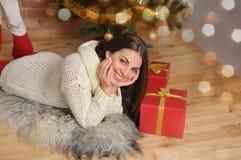 Den härliga le unga kvinnan med gåvor near julgranen Royaltyfria Foton