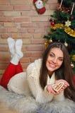 Den härliga le unga kvinnan med kakor near julgran a Fotografering för Bildbyråer