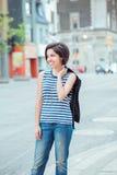 Den härliga le unga latinska latinamerikanska flickakvinnan med kort mörkt svart hår guppar, yttersidan i upptagen gata Royaltyfri Fotografi