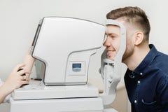 Den härliga le unga stilfulla mannen med mörkt hår passerar diagnostik av onspecial ögon- för intraocular tryck royaltyfria bilder