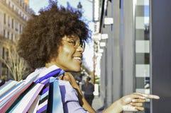 Den härliga le unga svarta kvinnan som rymmer shoppingpåsar på hennes skuldra och pekar på, shoppar Begrepp om shoppi arkivfoto