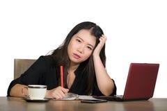 Den härliga ledsna och deprimerade asiatiska koreanska affärskvinnan som arbetar i spänning på känsla för skrivbordet för kontors arkivbild