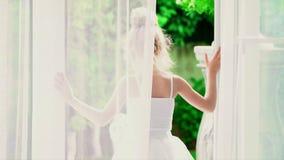 Den härliga lilla ballerina ser naturen utanför fönstret Lilla flickan i en vit ballerinakjol är vid fönstret stock video