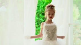 Den härliga lilla ballerina ser naturen utanför fönstret Lilla flickan i en vit ballerinakjol är vid fönstret lager videofilmer