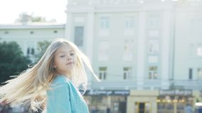 Den härliga lilla blondinen går och ler på kameran på stadsområdet stock video