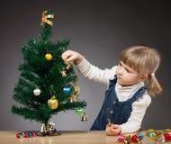 Den härliga lilla flickan dekorerar julgranen Arkivfoto