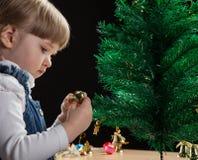 Den härliga lilla flickan dekorerar julgranen Arkivbilder