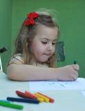 Den härliga lilla flickan drar något med färgpennorna royaltyfria foton