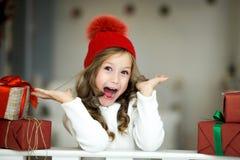 Den härliga lilla flickan firar jul Ferier för ` s för nytt år Lycklig flicka i en juldräkt med gåvan Arkivbilder