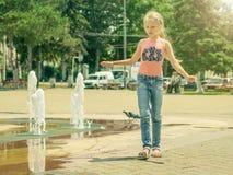 Den härliga lilla flickan går nära stadsspringbrunnen Fotografering för Bildbyråer