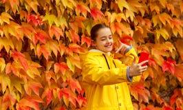 Den härliga lilla flickan i gul regnrock tar selfie på ljus bakgrund för höstsidor royaltyfria foton