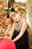 Den härliga lilla flickan klädde som en katt med ballonger i händer Sött leende, en mjuk blick Royaltyfri Fotografi