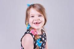 Den härliga lilla flickan ler ett tandlöst leende royaltyfri foto