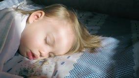 Den härliga lilla flickan med blont hår som sover på sängen och tänder av solens strålar, täckte med en beige filt lager videofilmer