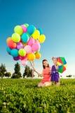 Den härliga lilla flickan med modern färgade ballonger och regnbåge u Royaltyfri Bild