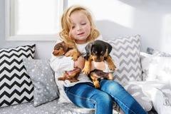Den härliga lilla flickan omfamnar två lilla charmiga valpar av en tax arkivbilder