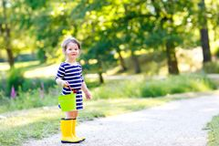 Den härliga lilla litet barnflickan som in spelar, parkerar Kläder för mode för förtjusande barn bärande tillfällig och gula gumm Fotografering för Bildbyråer