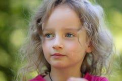 Den härliga lilla lockiga blonda flickan, har det allvarliga uttryckt, blicken in i avståndet, stora blåa ögon, långa ögonfrans Arkivbilder
