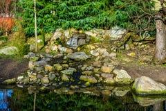 Den härliga lilla vattenfallet som göras av olika stenar, naturligt arbeta i trädgården garneringar arkivfoto
