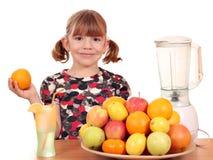 Liten flicka gör fruktfruktsaft Arkivbild