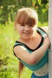 Den härliga liten flicka ser ut från hörnet o Royaltyfria Foton