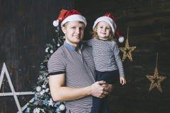 Den härliga liten flickabarndottern med faderjul är lycklig i hemmet royaltyfria foton