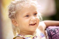 Den härliga liten flickablondinen ler på en färgrik bakgrund royaltyfri foto
