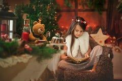 Den härliga liten flickabrunetten läste julberättelser till hennes leksaknallebjörn arkivbild