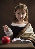 Den härliga liten flickakristen, iklädd gammal kläder som läser bibeln, handgesterna, markerar ord och huvudsakliga idéer fotografering för bildbyråer