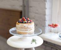 Den härliga ljusbruna kakan med vitkräm som dekoreras med jordgubbar och blåbär på en vit sockel, står på fönstret arkivbilder