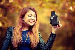 Den härliga ljust rödbrun flickan ler till den parallella kameran Arkivfoton
