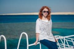Den härliga ljust rödbrun kvinnan i solexponeringsglas sitter på en vit yacht i ett hav med klart turkosvatten Avkoppling på somm Arkivbilder