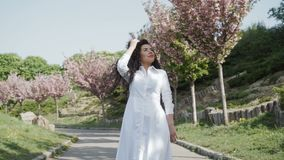 Den härliga lockiga brunetten i den vita klänningen som går, i att blomma, parkerar stock video