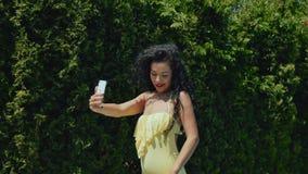 Den härliga lockiga brunetten med röda kanter gör selfie på grön buskebakgrund lager videofilmer