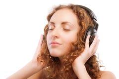 den härliga lockiga flickan lyssnar musik till arkivbild