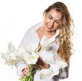 Den härliga lockiga flickan med våren blommar tulpan på en vit bakgrund Fotografering för Bildbyråer