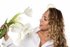Den härliga lockiga flickan med våren blommar tulpan på en vit bakgrund Royaltyfri Fotografi