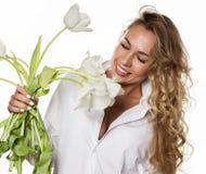 Den härliga lockiga flickan med våren blommar tulpan på en vit bakgrund Royaltyfri Bild