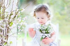 Den härliga lockiga litet barnflickan med den första våren blommar Arkivbilder