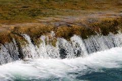 Den härliga lugna klara vattenfallet för flodvatten med synligt vaggar och rent vitt skum royaltyfria foton