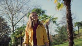 Den härliga lyckliga flickan i ett gult omslag promenerar avenyn med palmträd på en solig dag lager videofilmer