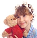 Den härliga lyckliga flickan omfamnar en toybjörn Royaltyfri Bild