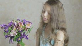Den härliga lyckliga flickan tycker om bukettblommor av iriers och alstroemeria stock video