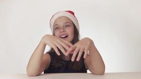Den härliga lyckliga flickatonåringen i en Santa Claus hatt drömmer och sjunger joyfully på den vita videoen för bakgrundsmaterie stock video