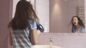 Den härliga lyckliga flickatonåringen torkar hår med hårtorken och sjunger och dansar framme av en spegel i badrummaterielet stock video