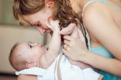 Den härliga lyckliga modern som spelar med nyfött, behandla som ett barn Arkivbild