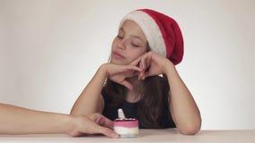 Den härliga lyckliga tonåriga flickan i drömmar för en Santa Claus hatt av en gåva, mottar en festlig kaka och uttrycker missnöje stock video