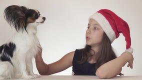 Den härliga lyckliga tonårs- flickan i en Santa Claus hatt förvånas och tycker om denväntade på gåvan - dog den kontinentala leks stock video