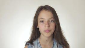 Den härliga lyckliga tonårs- flickan ser och är den förvånade närbilden på den vita videoen för bakgrundsmateriellängd i fot räkn stock video