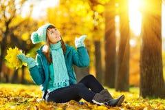 Den härliga lyckliga unga kvinnan i hösten parkerar Glad kvinnawea Arkivbilder